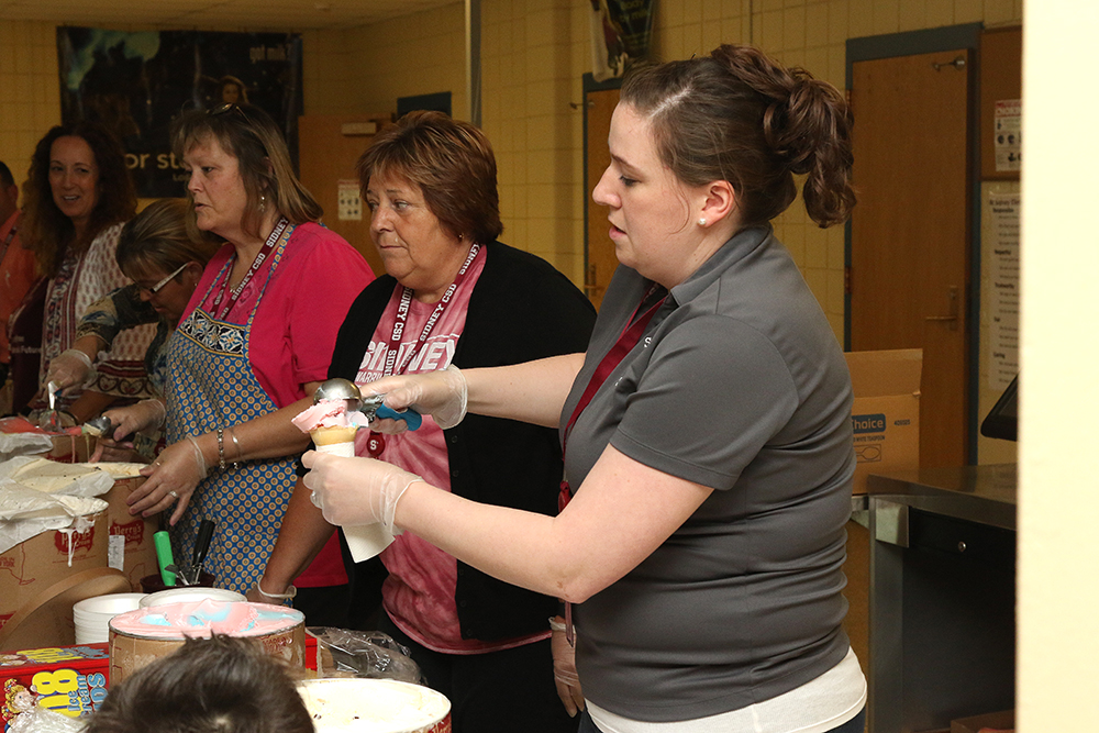 Staff member scooping out ice cream