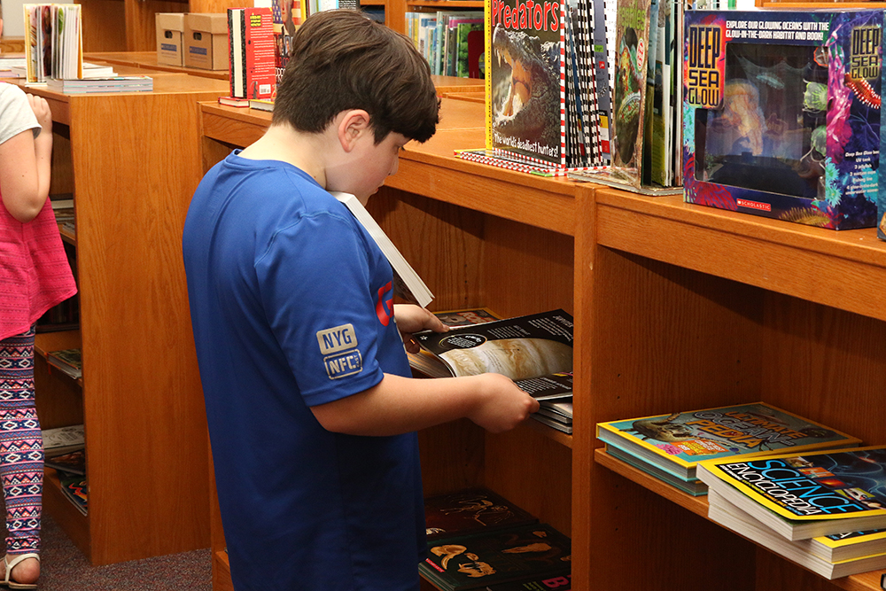 Student looking at books at book fair