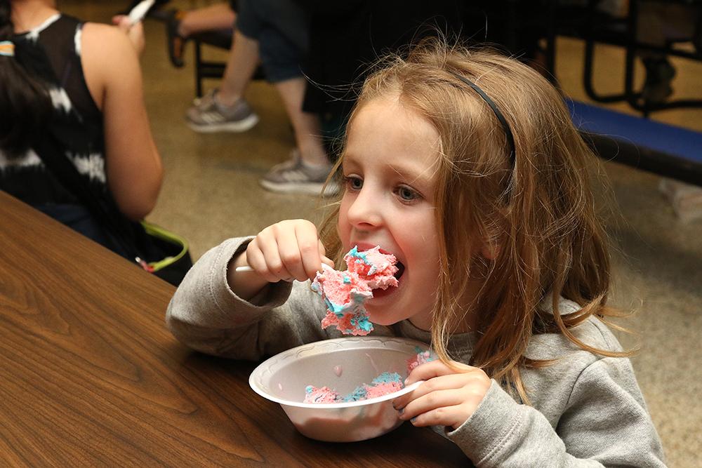 Child taking big bite of ice cream
