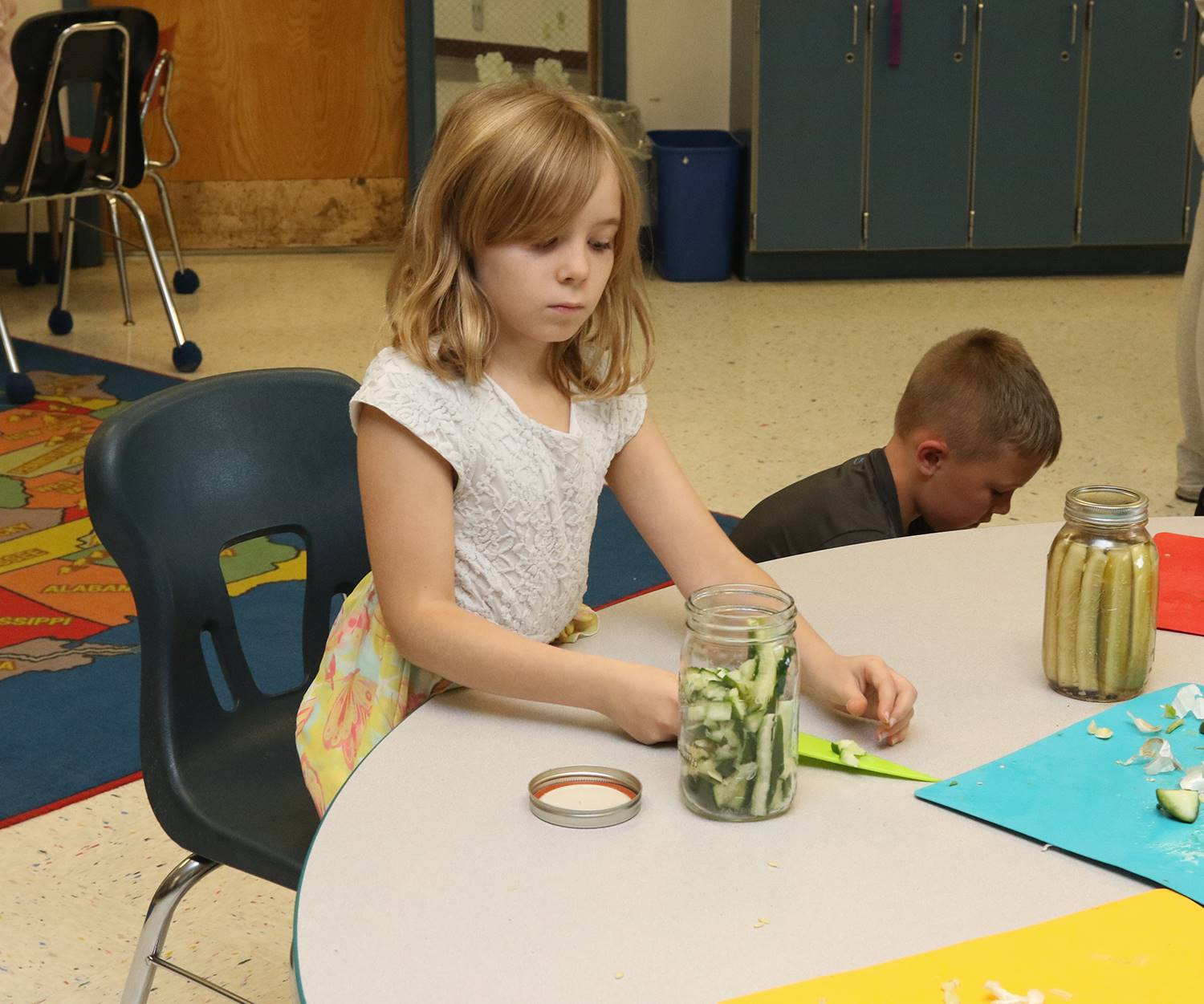Elementary students making pickles