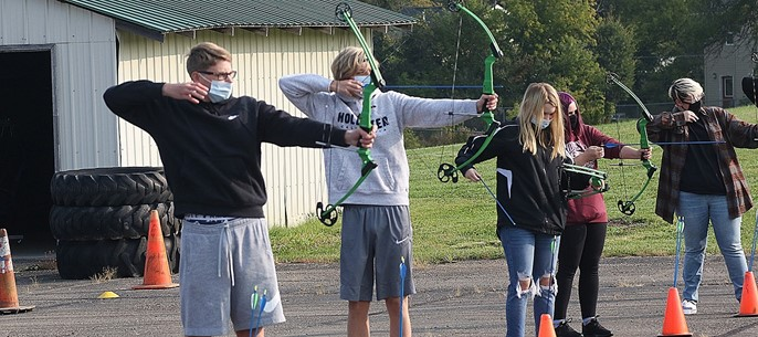 High school PE class learning archery