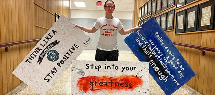 Student with ceiling tile project